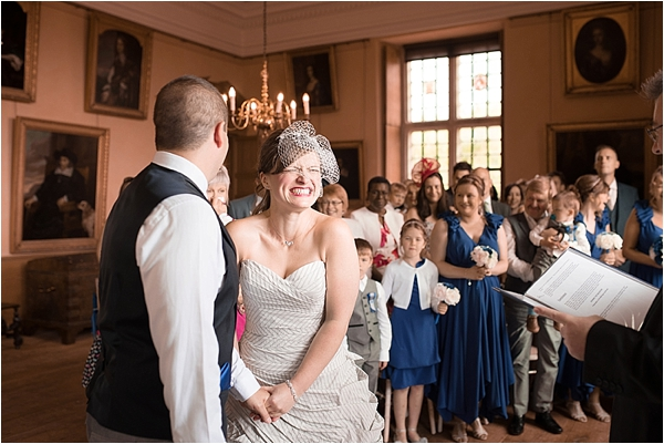 A bride and grrom at the top of the aisle at Lodge Park smiling
