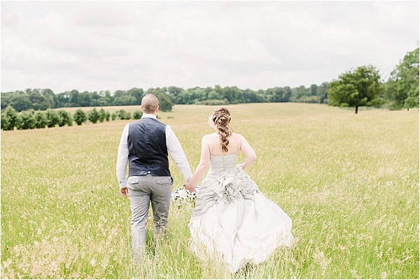 A bride and groom outside lodge park walking in the long grass